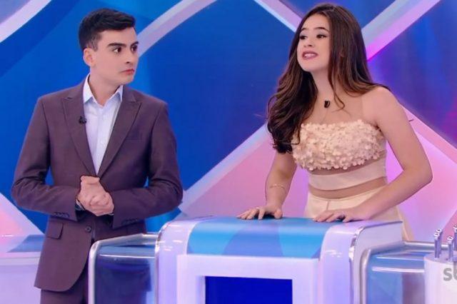 Maisa falando durante programa do Silvio Santos e Dudu olhando para ela