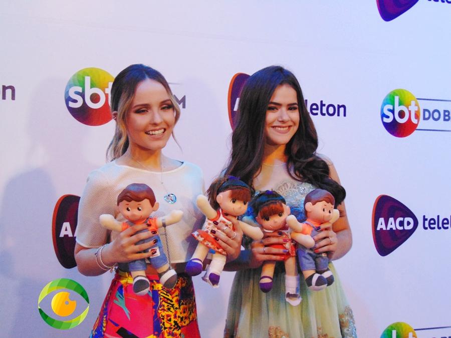 Duas jovens garotas estão sorridentes e seguram bonecos nas mãos