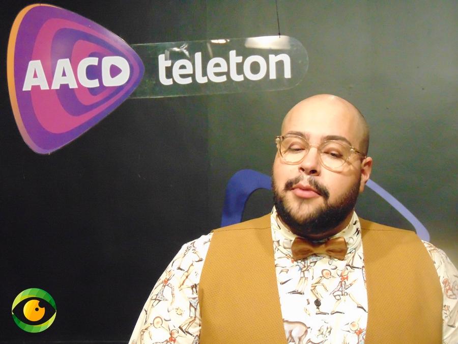 Fundo preto, logo da Associação de Assistência à Criança Deficiente, homem careca e barbudo de colete e gravata borboleta está falando