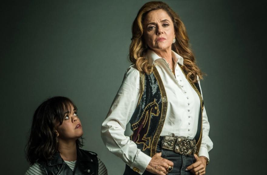 """Do lado esquerdo, atriz anã olhando para mulher com semblante sério, ambas personagens da novela """"O Outro Lado do Paraíso"""""""