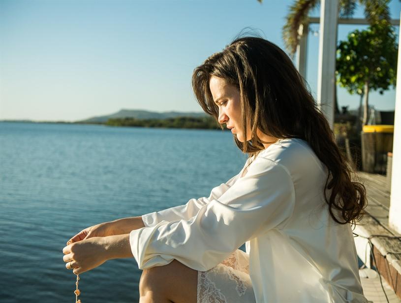 mulher sentada segurando um terço frente ao mar