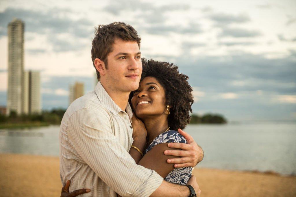 homem branco e mulher negra sorridente abraçados em meio a uma paisagem