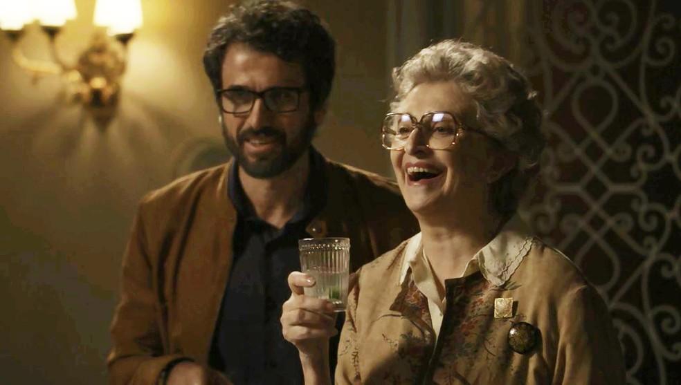 """em um cenário de novela """"O Outro Lado do Paraíso"""", um homem branco barbudo e usando óculos está em pé ao lado de uma mulher mais velha sorridente"""