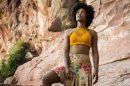 linda mulher negra olhando para o horizonte fundo da imagem há paisagem rochosa, atriz de O Outro lado do Paraíso