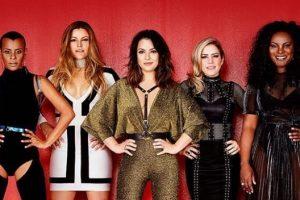 Cinco mulheres em pé em frente a um pano de fundo vermelho
