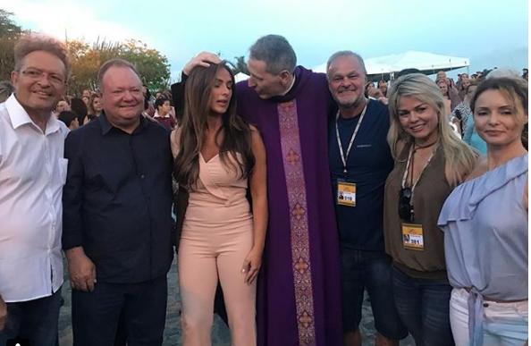 Celebridades. Foto do site da O TV Foco que mostra Nicole Bahls recebe bênção de padre antes da estreia em peça bíblica