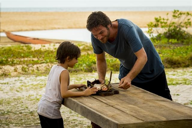 Beto (Emilio Dantas) e Ícaro (Thales Miranda) grelham e comem peixe na areia (Foto: Globo/João Cotta)