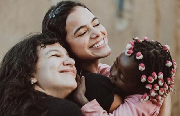 Bruna Marquezine e Priscilla Alcântara se encantam com menina na Angola (Foto: Vatanabe Cruz)