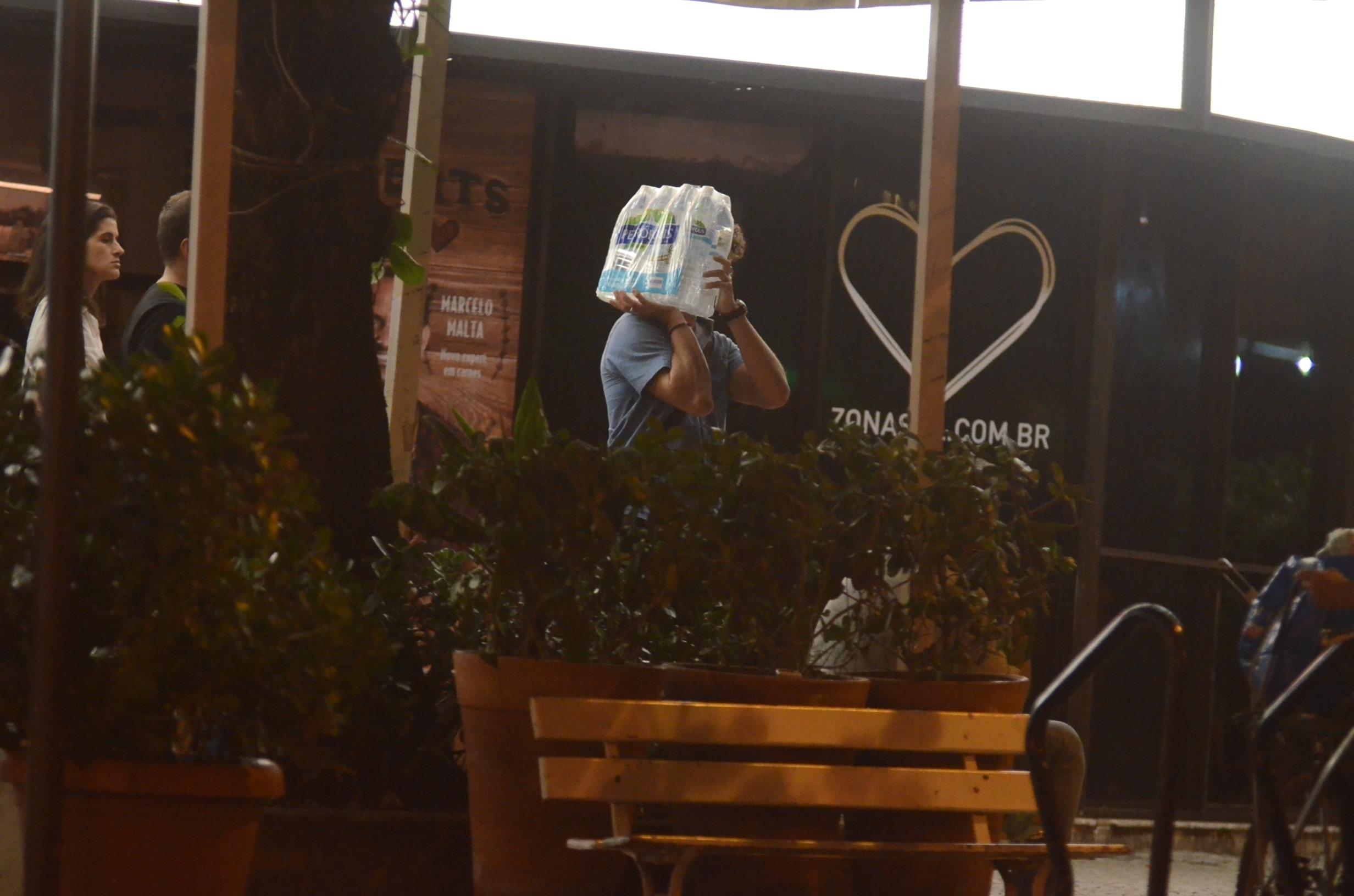 José Loreto saindo de estabelecimento com as águas que comprou (Foto: AGNews)