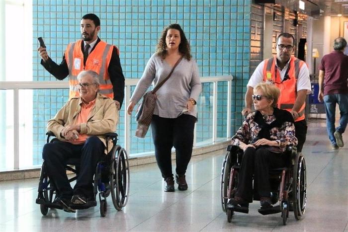 Tarcísio Meira e Gloria Menezes embarcam de cadeira de rodas no aeroporto Santos Dumont no Rio (Foto: Audrey Assed/AgNews)
