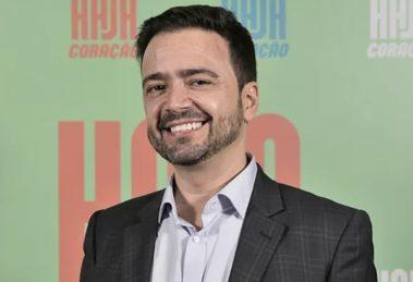 Daniel Ortiz sorridente em frente a banner de Haja Coração