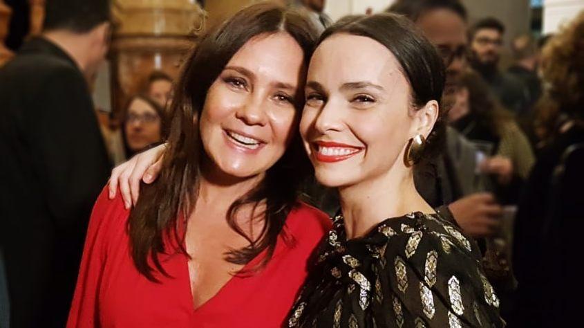 Na foto estão as atrizes Adriana Esteves e Debora Falabella sorridentes