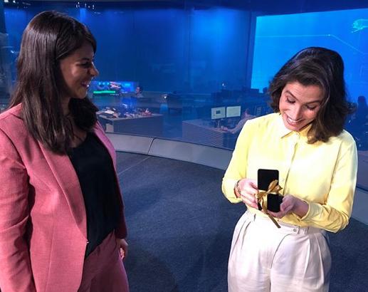 A jornalista Renata Vasconcellos ao receber uma joia da colega Jessica Senra (Foto: Reprodução)