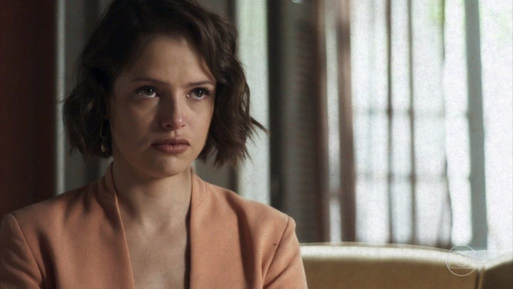 A atriz Agatha Moreira em A Dona do Pedaço usa blazer laranja e encara com expressão de descaso
