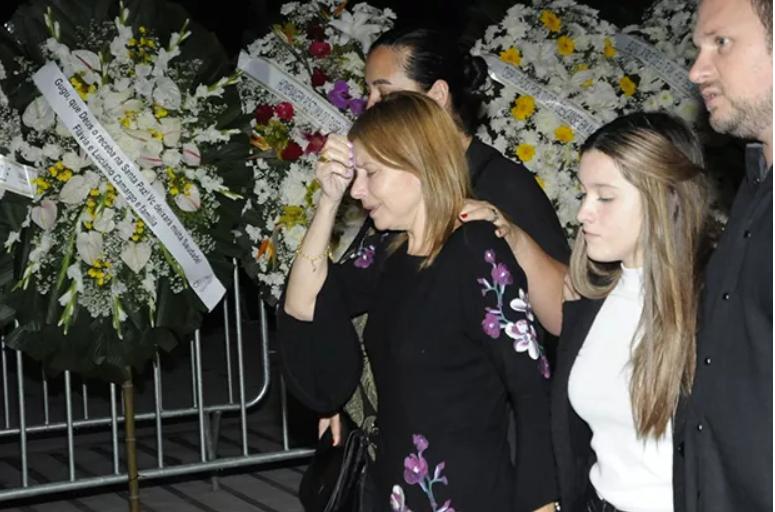 Viúva de Gugu e sua filha saem do velório (Foto: Reprodução)