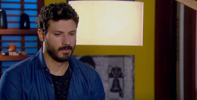 Personagem de As Aventuras de Poliana, Marcelo em cena de cabeça abaixada, ele usa camisa social azul e barba