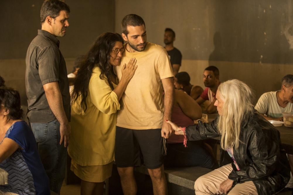 Lurdes abraça e beija Sandro, chora. Magno (Juliano Cazarré) tenta acalmar a mãe em Amor de Mãe