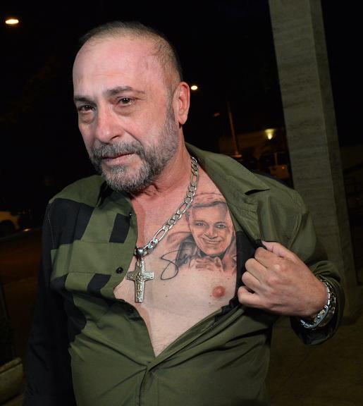 Amigo de Gugu, o diretor Goiabinha, exibe tatuagem do apresentador na missa do sétimo dia (Foto: Reprodução)