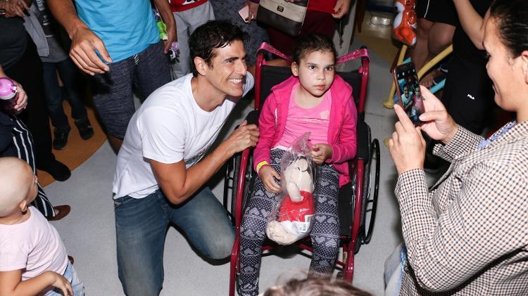 Reynaldo Gianecchini da Globo ao lado de criança da GRAACC (Foto: Lucas Ramos / AgNews)