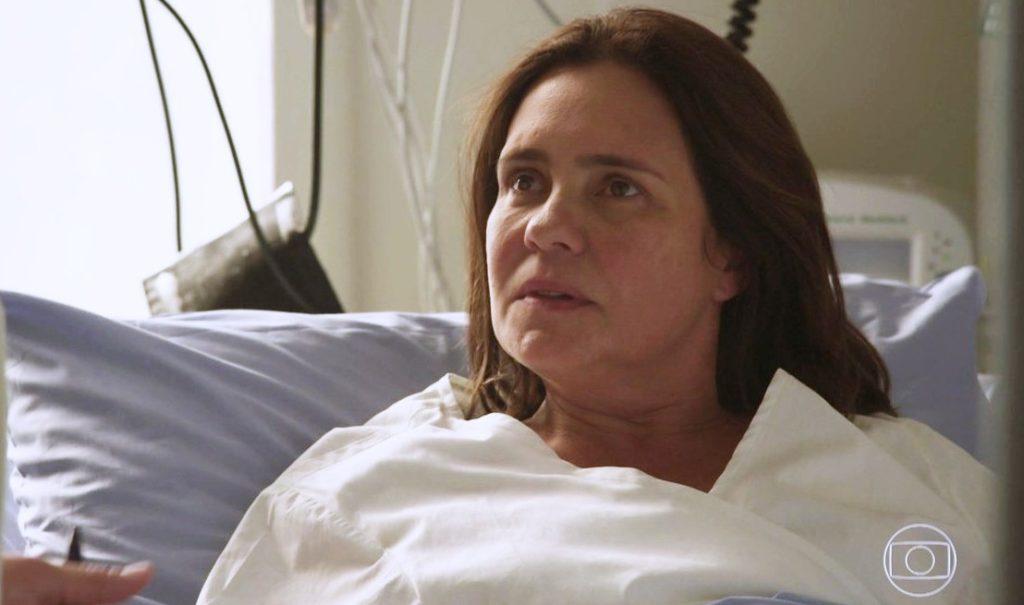 Atriz Adriana Esteves deitada na cama de um hospital em cena da novela Amor de Mãe da Globo