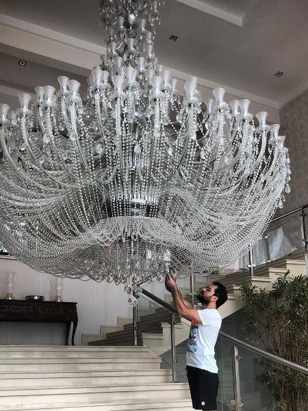 Luciano Camargo limpando o lustre de sua mansão de 28 milhões de reais (Foto reprodução Instagram)