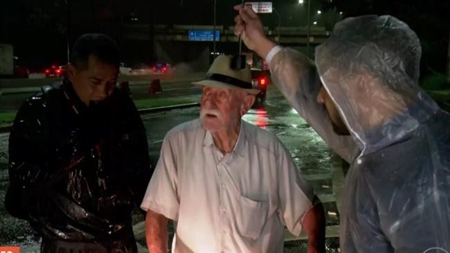 Idoso recebe ajuda em meio a alagamento em São Paulo por equipe de reportagem (Foto: Reprodução/Globo)