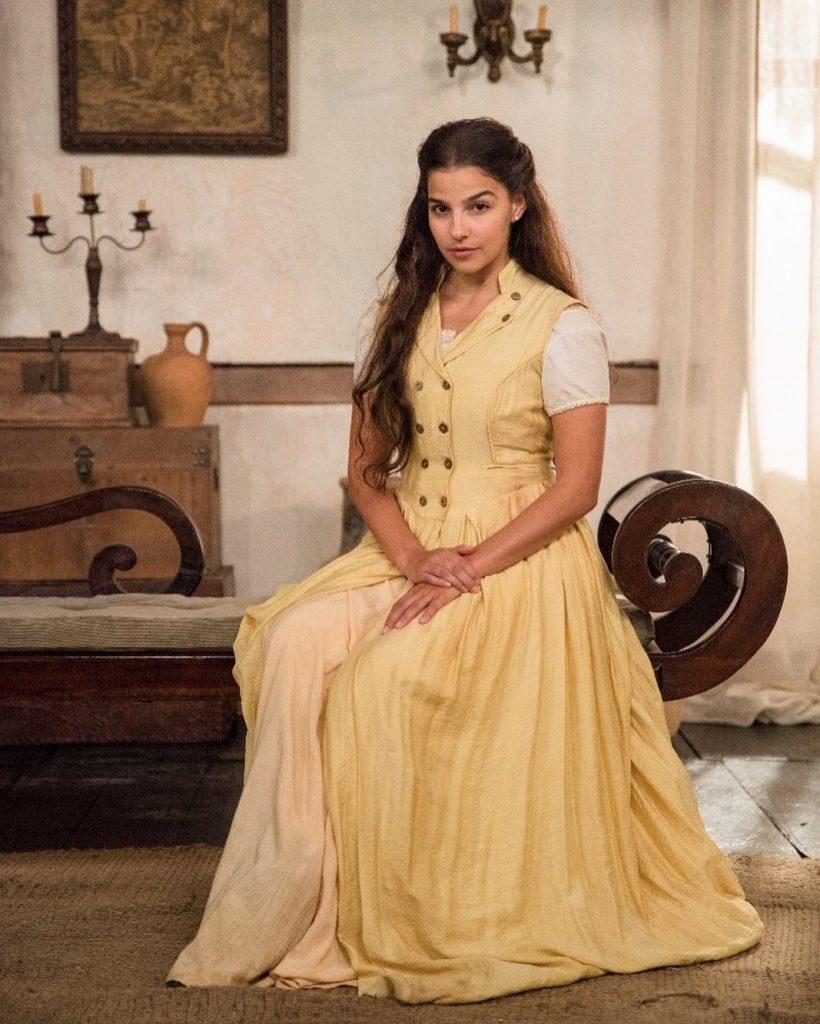 Atriz Gabriela Medvedovski usa vestimentas de época para sua personagem Pilar de Nos Tempos do Imperador em um cenário com móveis antigos