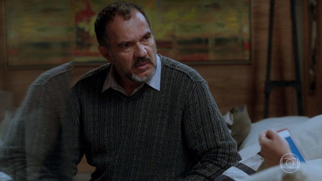 Germano sentado em cena da novela Totalmente Demais
