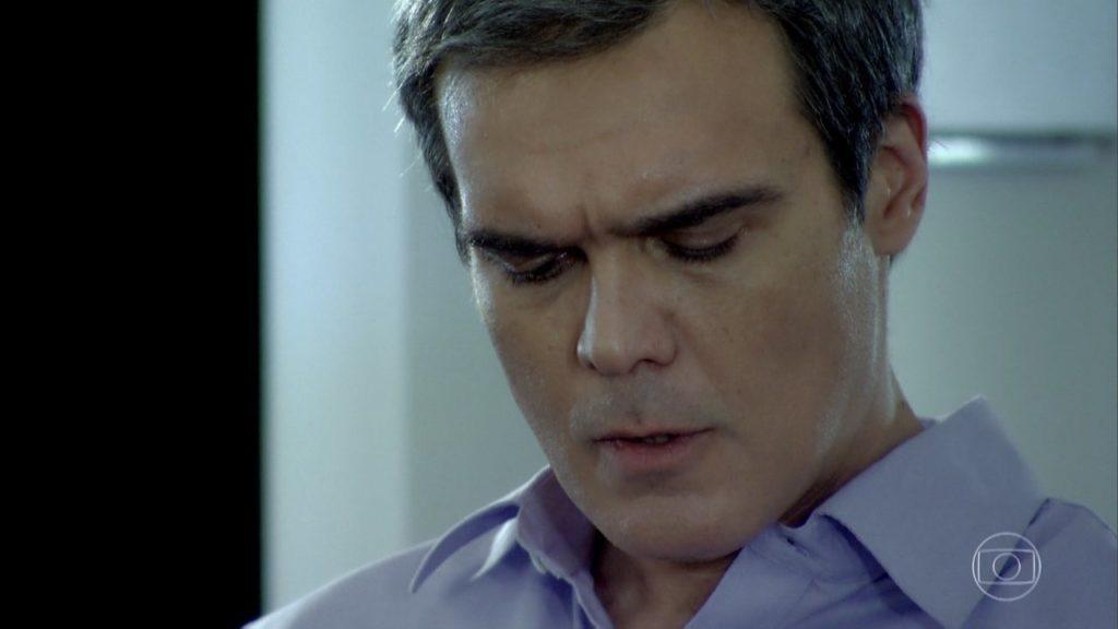 Na novela Fina Estampa o personagem René tem expressão séria e olha para baixo