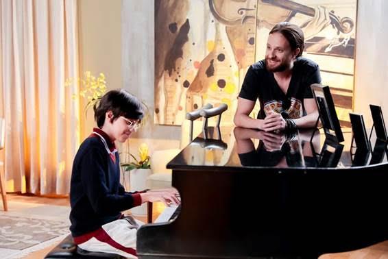 Bento está sentado a frente do piano e Cássio encostado sob o objeto em cena da novela As Aventuras de Poliana