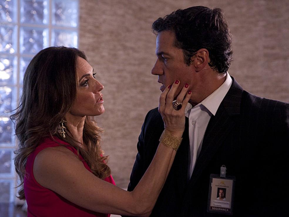 Tereza Cristina de vestido vermelho em cena da novela Fina Estampa aperta o rosto de Ferdinand de terno escuro com crachá pendurado com a mão