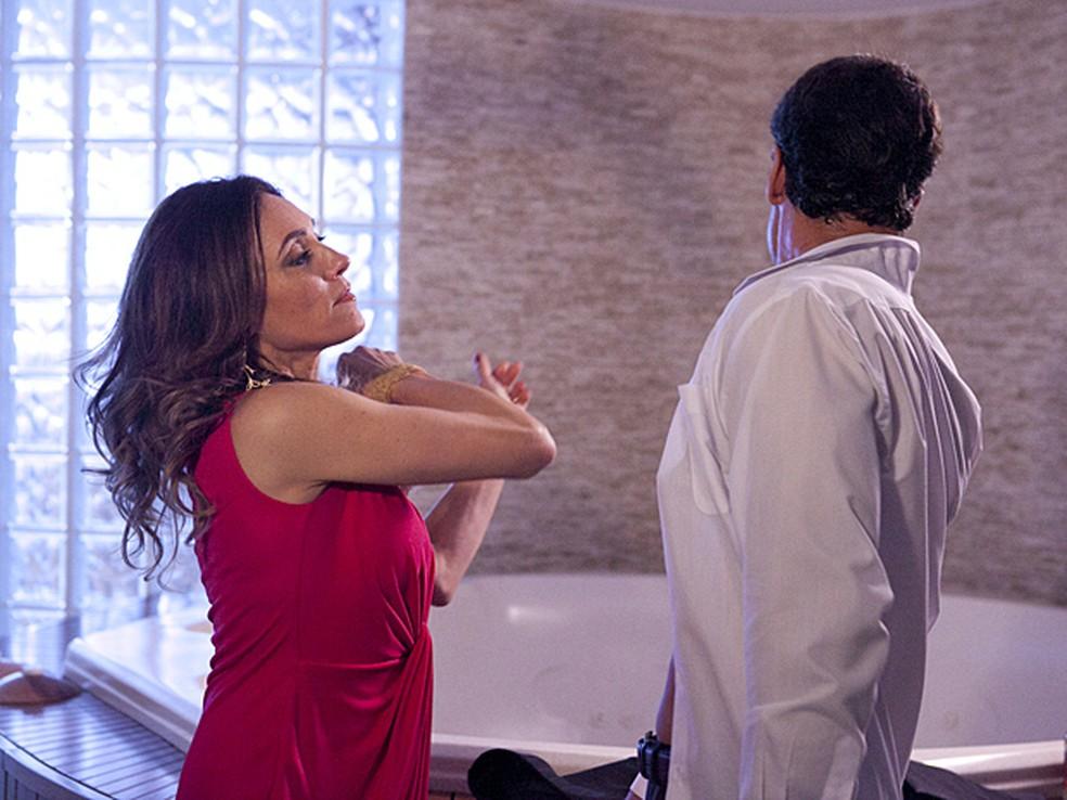 Tereza Cristina em Fina Estampa tem braço curvado após bater em Ferdinand que está com o rosto e o corpo virado