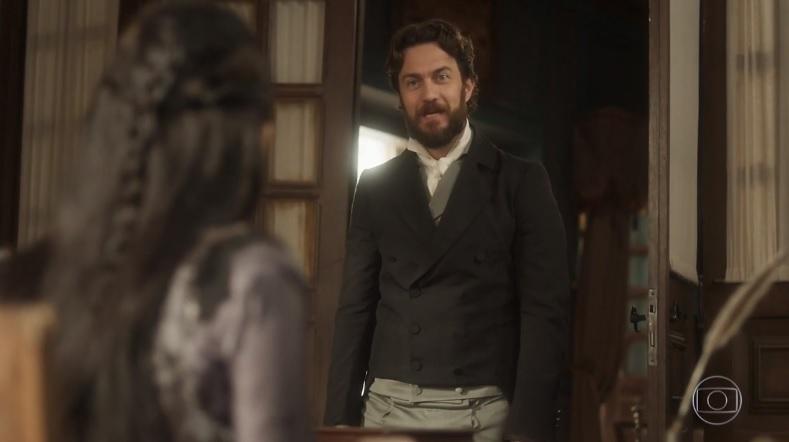 Thomas com trajes de militar de época em pé observando mulher sentada em cena da novela Novo Mundo
