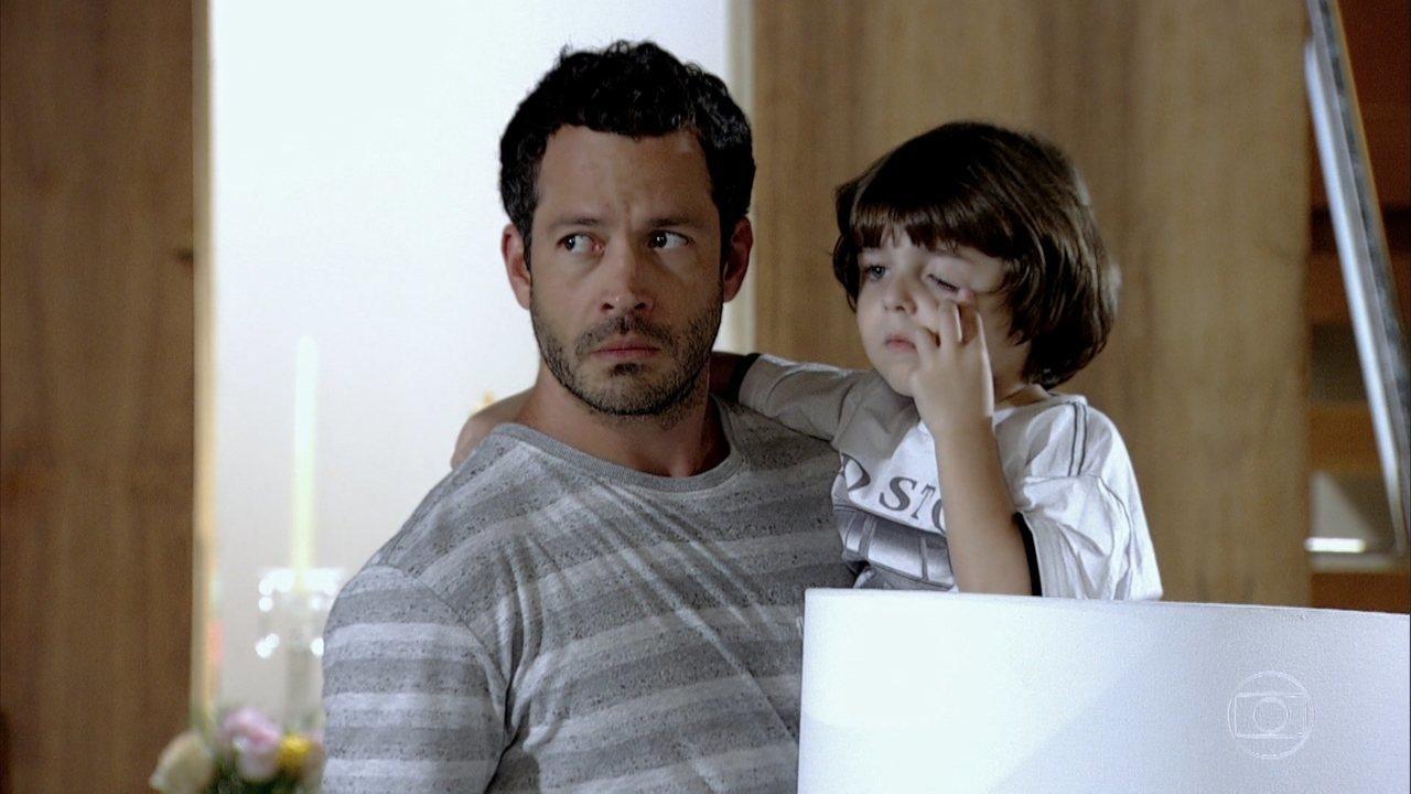 Quinzé com cara de desconfiado segura seu filho que coça o olho em cena da novela Fina Estampa