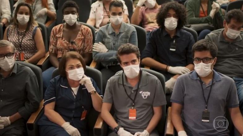 Pessoas diversas estão sentadas em um mini teatro em cena de Salve-se Quem Puder usando máscaras nos rostos e luvas