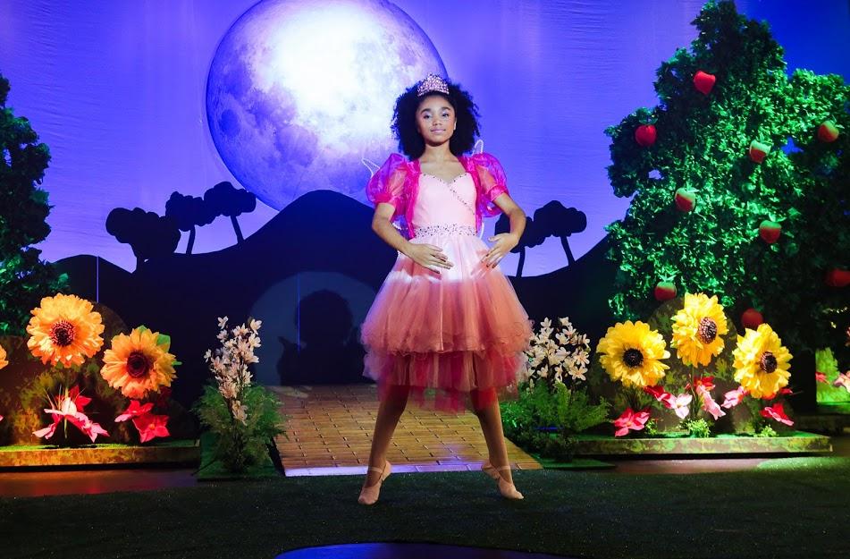 Cenário colorido de uma peça de teatro onde Kessya de As Aventuras de Poliana está no centro em pose de bailarina e vestido rosa