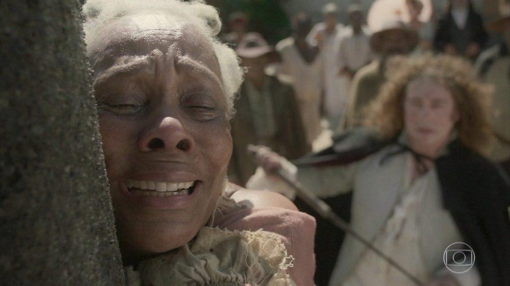 Idalina chora após ser chicoteada no tronco na novela Novo Mundo