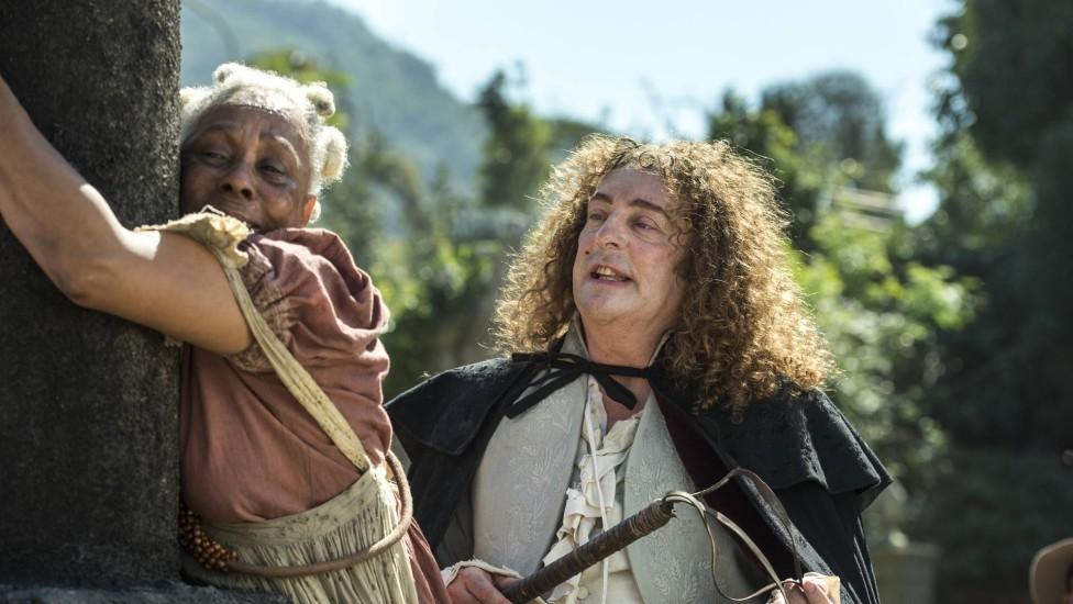 Idalina amarrada em tronco e Sebastião com chicote nas mãos a olha com repulsa em cena de Novo Mundo