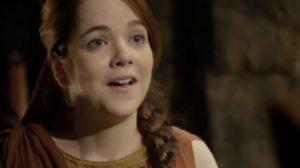 Em cena da novela Jesus, Diana, moça branca de cabelo ruivo com trança, tem expressão surpresa