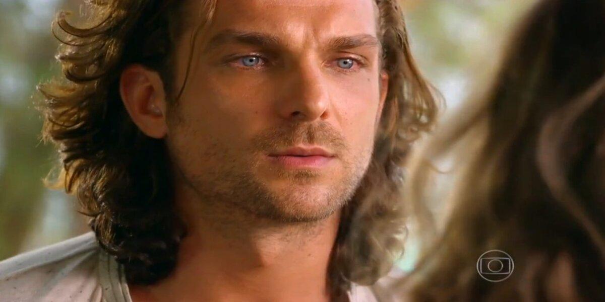 Close no rosto de Alberto, personagem da novela Flor do Caribe, homem branco, de barba olhos claros azuis e cabelo comprido