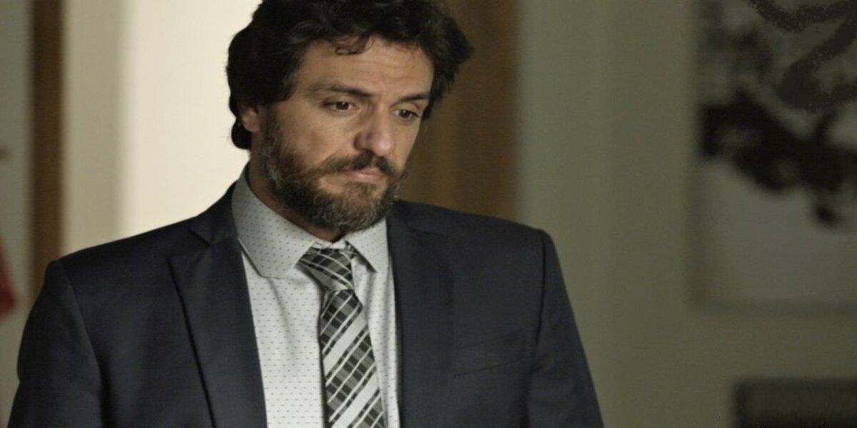 Rodrigo Lombardi em cena da novela A Força do Querer, ele usa terno cinza escuro, camisa social clara e gravada quadriculada, barba e tem expressão de dúvida