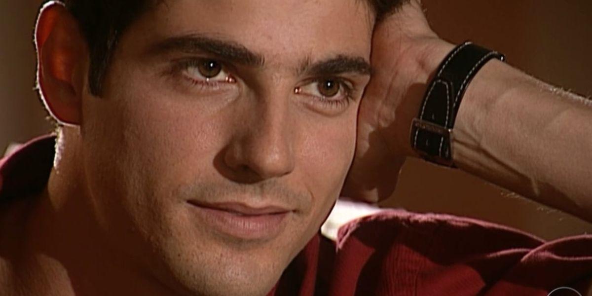 Na imagem close no rosto de Edu de Laços de Família, homem branco de olhos castanhos usando camisa vermelha e rosto apoiado na palma da mão