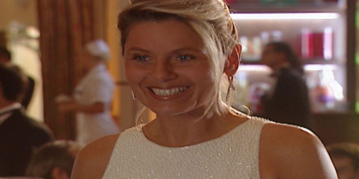Helena de Laços de Família está sorridente usando um vestido brilhoso sem mangas em cena da novela do Vale a Pena Ver de Novo