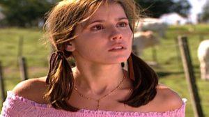 Íris em Laços de Família está vestindo uma blusa cor de rosa, usa o cabelo liso em duas partes amarrado e está ao ar livre em fazenda no fundo desfocada