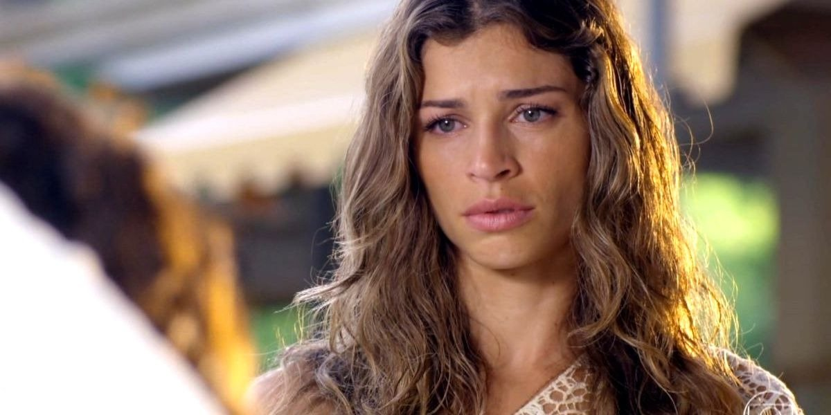 Ester observa algo em cena da novela Flor do Caribe com expressão preocupada