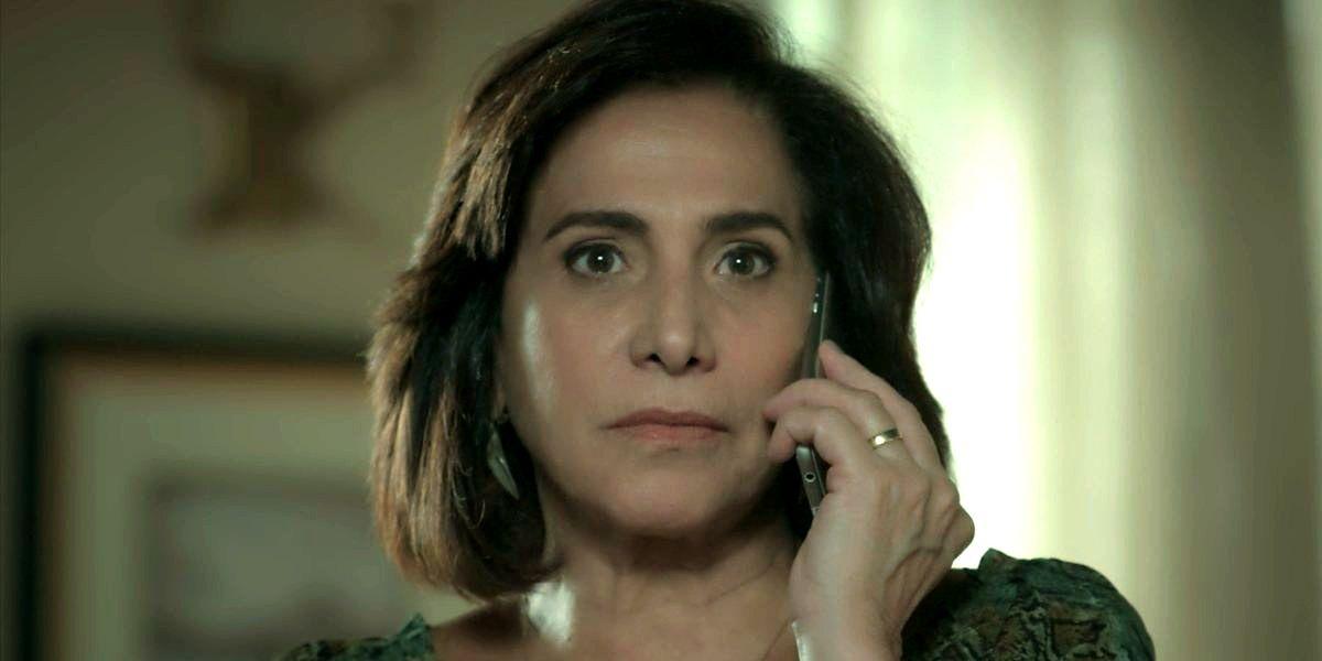 Heleninha usa o celular com a mãe esquerda que tem uma aliança de ouro no dedo anular em cena de A Força do Querer