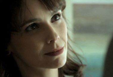 Irene, mulher branca de cabelo castalho escuro, branca e de batom roxo, dá sorriso irônico em cena de A Força do Querer