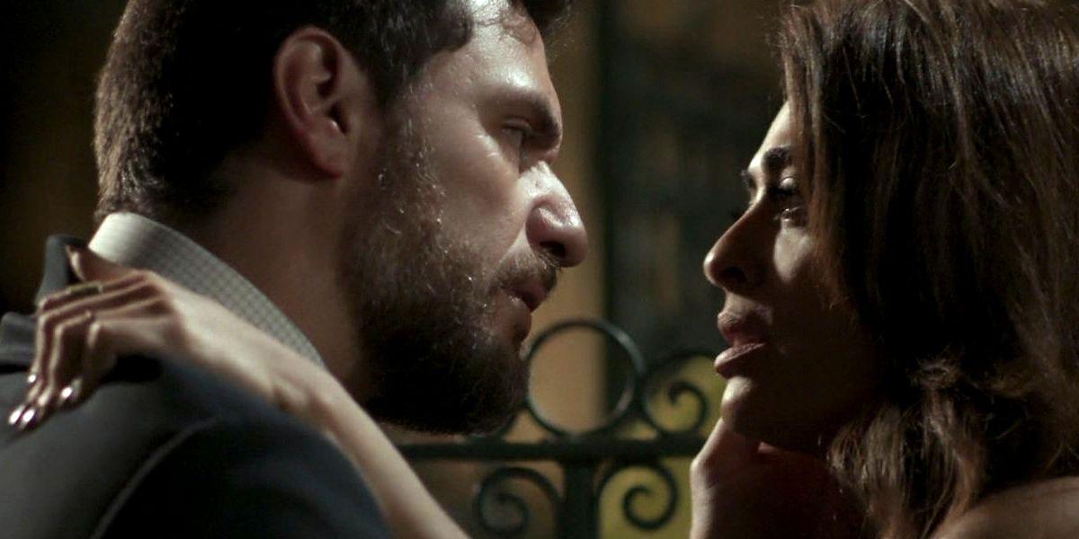 Perfis de Caio e Bibi, ele segura o rosto dela e ela aperta o ombro dele em cena da novela A Força do Querer