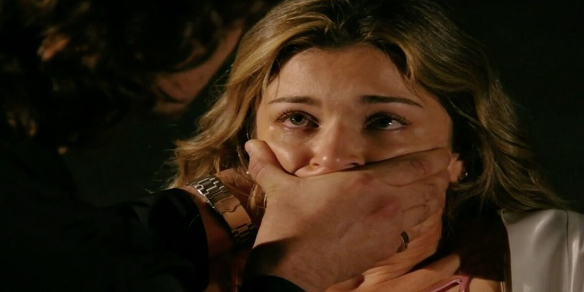 Ester, protagonista da novela Flor do Caribe, tem o rosto esmagado por a mão de um homem