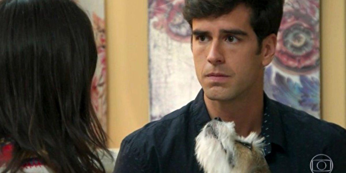 Felipe em cena de Haja Coração segurando cachorrinho